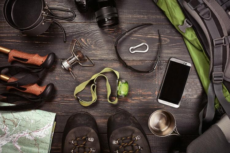 Hiking equipment lying on dark wood background