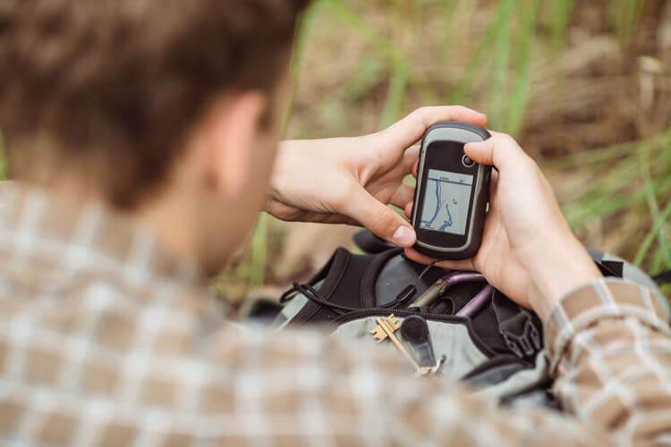 Man in woods using GPS tracker
