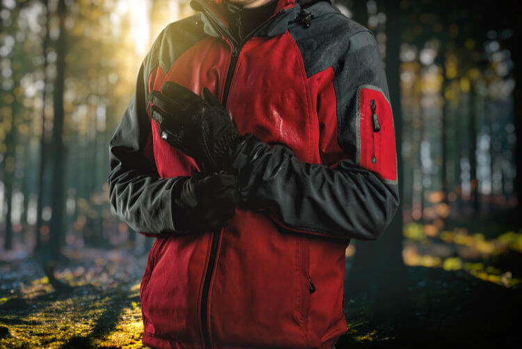 Man wearing waterproof jacket and gloves in the woods