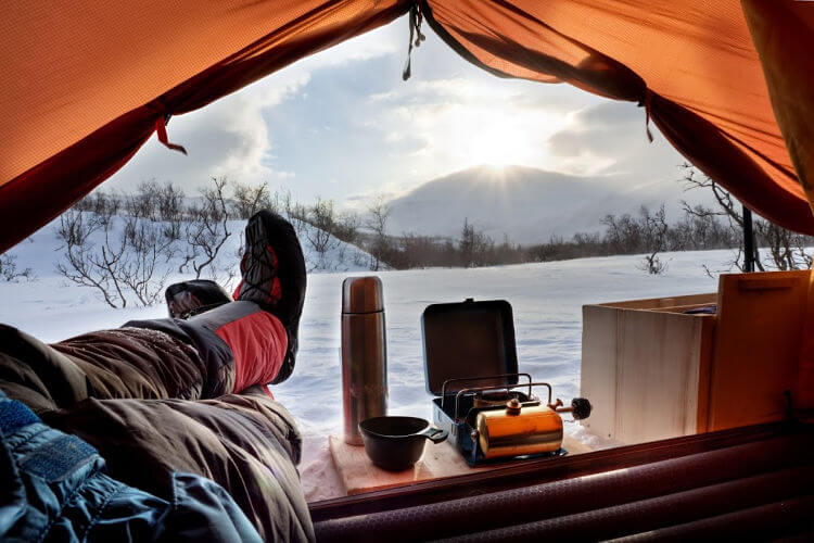 Camper in winter with feet up watching snowy landscape with flask and boots on
